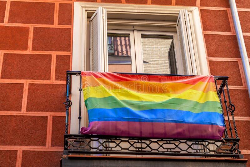 Bandiera omosessuale dell'arcobaleno sul balcone Vista della via Camera con fotografia stock libera da diritti