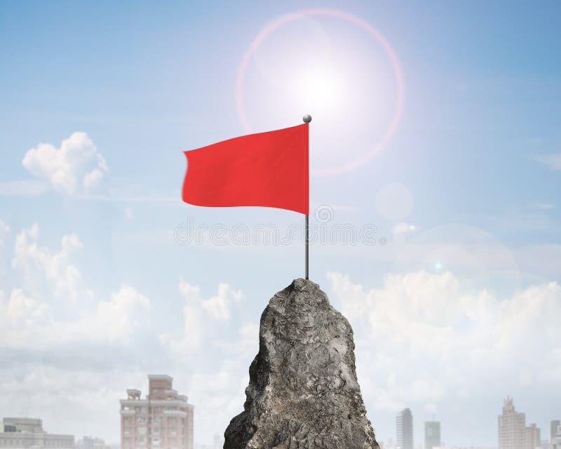 Bandiera ondulata rossa sopra il picco di montagna rocciosa immagine stock