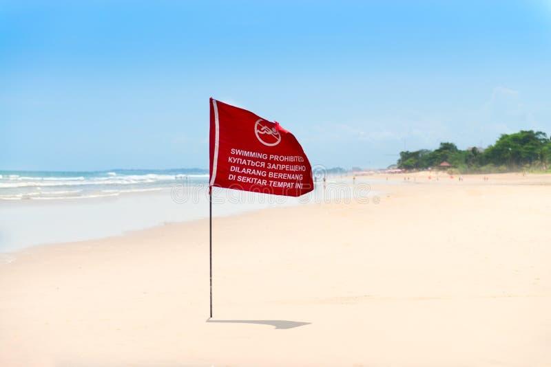 Bandiera rossa sulla spiaggia della sabbia fotografia stock libera da diritti