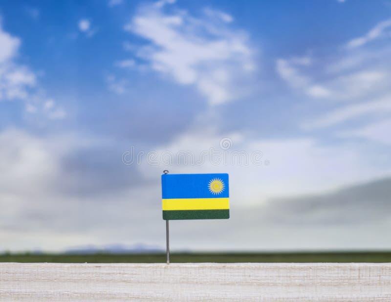 Bandiera ruandese con il vasto prato e cielo blu dietro  immagini stock libere da diritti