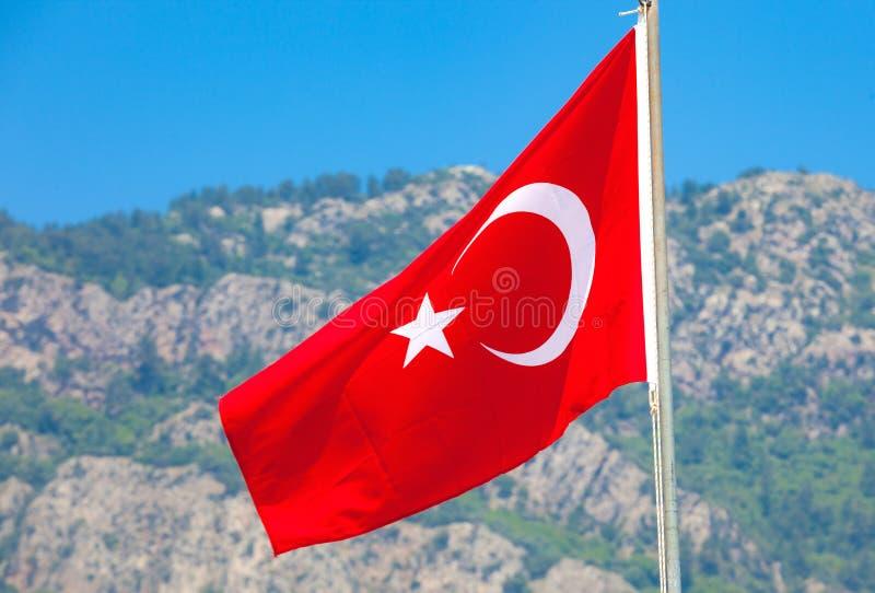 Bandiera turca su un fondo delle montagne fotografia stock