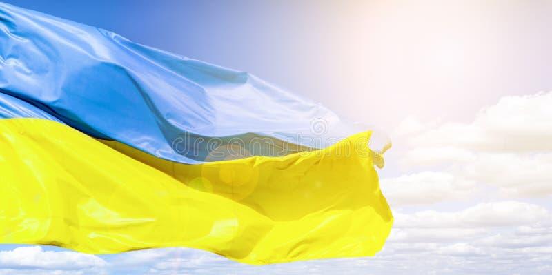 Bandiera ucraina contro un cielo nuvoloso blu Bandiera dell'Ucraina al sole e dell'abbagliamento La bandiera blu e gialla si svil immagine stock libera da diritti