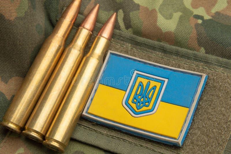 Bandiera ucraina sui precedenti di un rivestimento militare del cammuffamento immagini stock
