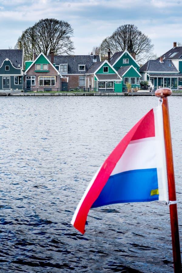 Bandiera vaga dei Paesi Bassi contro lo sfondo di un villaggio olandese tradizionale fotografia stock libera da diritti
