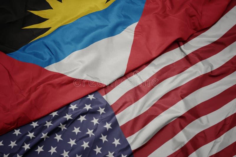 bandiera variopinta d'ondeggiamento degli Stati Uniti d'America e bandiera nazionale dell'Antigua e di Barbuda immagine stock libera da diritti