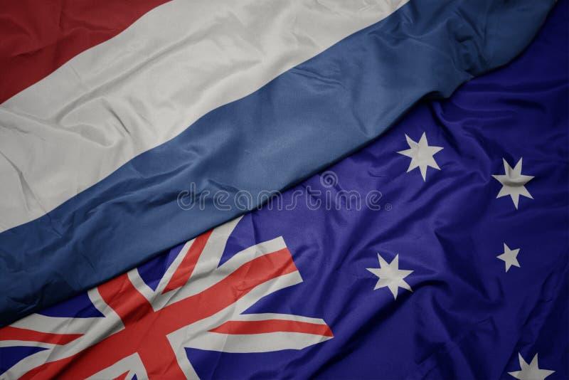 bandiera variopinta d'ondeggiamento dell'Australia e bandiera nazionale dei Paesi Bassi fotografia stock libera da diritti
