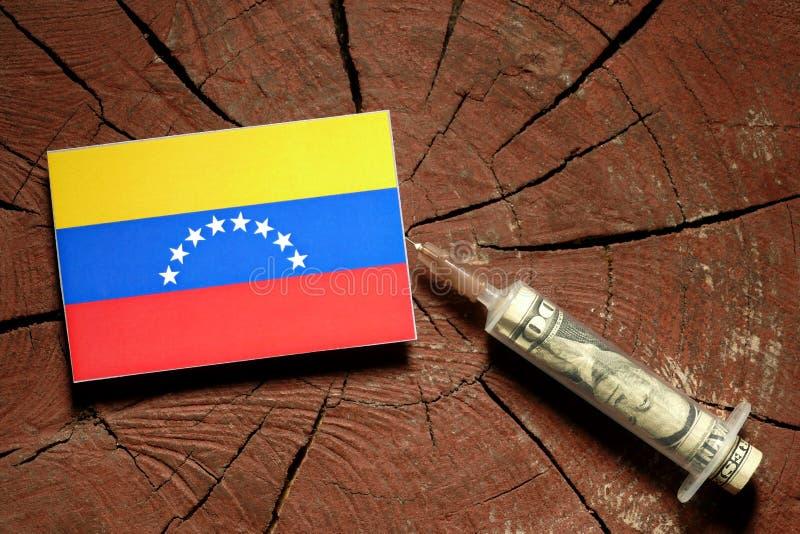 Bandiera venezuelana su un ceppo con la siringa che inietta soldi fotografia stock libera da diritti