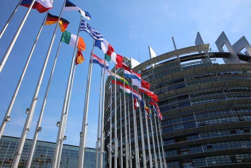 Bandiere dei membri di UE davanti alla costruzione del Parlamento Europeo a Strasburgo fotografia stock libera da diritti