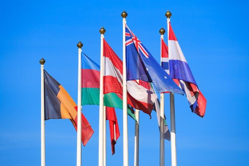 Bandiere dei paesi differenti contro un cielo luminoso fotografie stock libere da diritti
