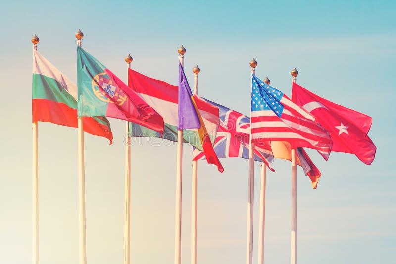 Bandiere dei paesi differenti sulle aste della bandiera bianche fotografia stock