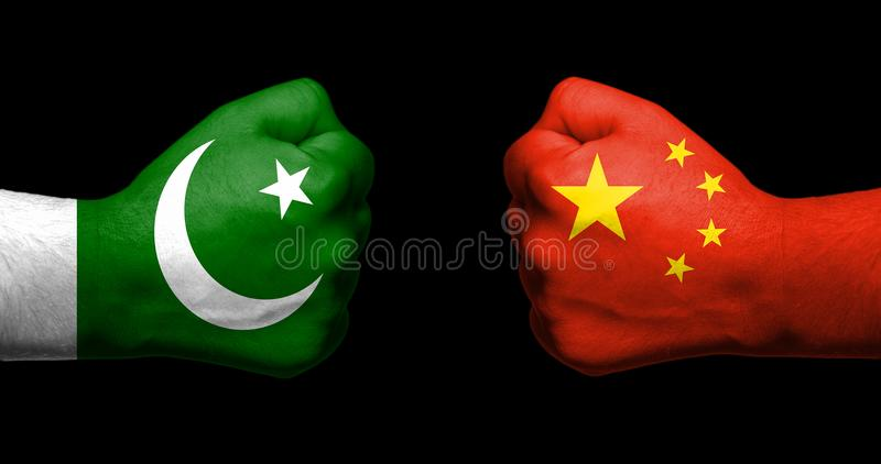 Bandiere del Pakistan e della Cina dipinti su un affronto di due pugni chiusi fotografia stock