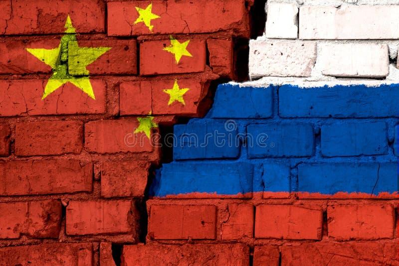 Bandiere della Cina e della Russia sul muro di mattoni con la grande crepa nel mezzo Simbolo dei problemi fra i paesi fotografia stock libera da diritti