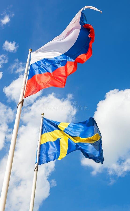 Bandiere della Svezia e del Russo che ondeggiano contro il cielo immagine stock