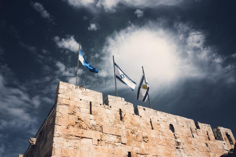 Bandiere di Gerusalemme e di Israele sui vecchi mura di cinta di Gerusalemme contro il cielo blu con le nuvole bianche alla luce  immagine stock libera da diritti