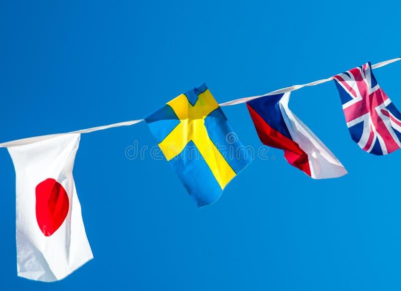 bandiere nazionali differenti che appendono su una corda su un fondo del cielo blu fotografie stock