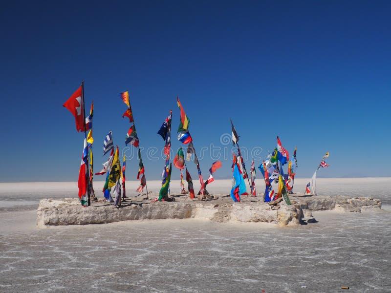 Bandiere in Salar de Uyuni, Bolivia fotografia stock libera da diritti