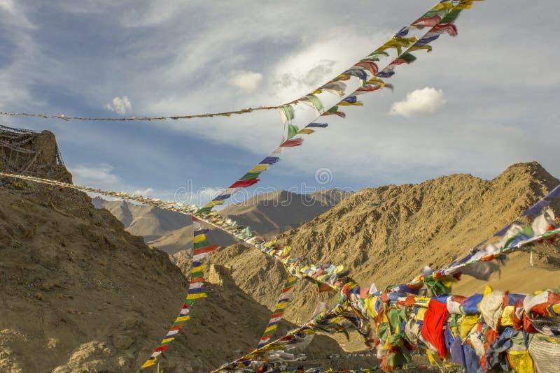 Bandiere tibetane di una preghiera nel cielo contro il contesto delle montagne himalayane del deserto immagine stock libera da diritti