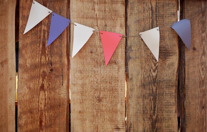 Bandiere variopinte festive contro i precedenti di legno di lerciume Festa dell'indipendenza in U.S.A. fotografie stock libere da diritti