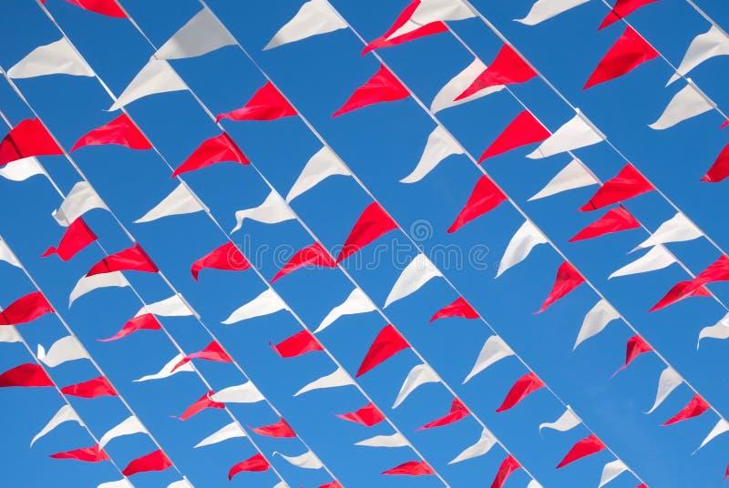 Bandiere variopinte rosse e bianche su cielo blu immagine stock libera da diritti