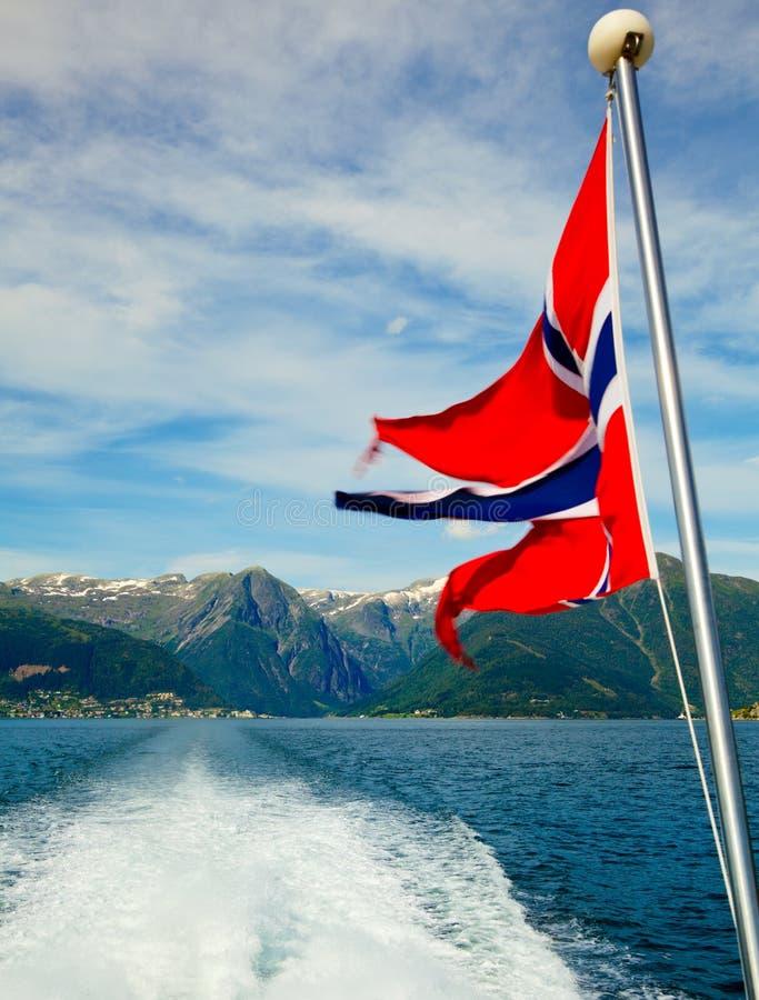 Bandierina norvegese contro le montagne del fiordo fotografia stock
