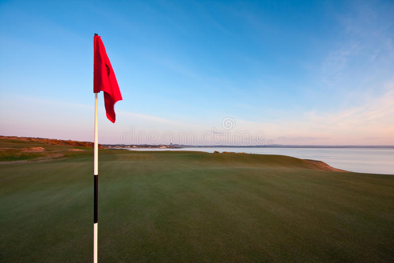 Bandierina rossa di golf su un verde all'alba immagine stock libera da diritti