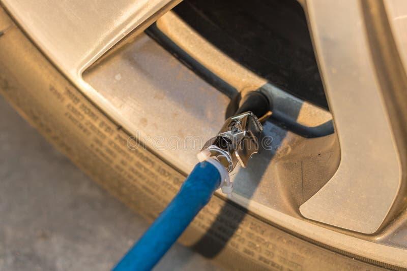 Bandinflatie Het vullen van lucht in een autoband stock foto's