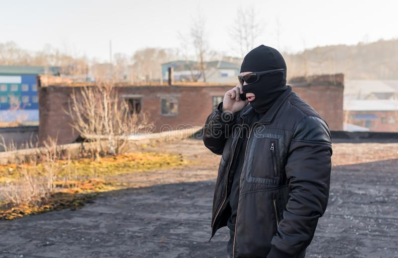 A bandit in a black leather jacket and a mask talking on the phone on the street near an abandoned building. A man, a terrorist, a bandit in a black leather royalty free stock photo