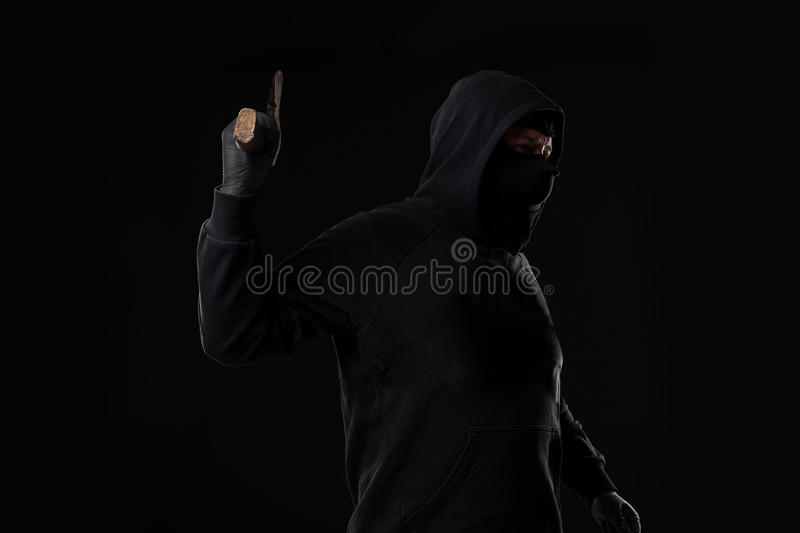 Bandit in black mask with hatchet on black background. Masked man with an ax royalty free stock images