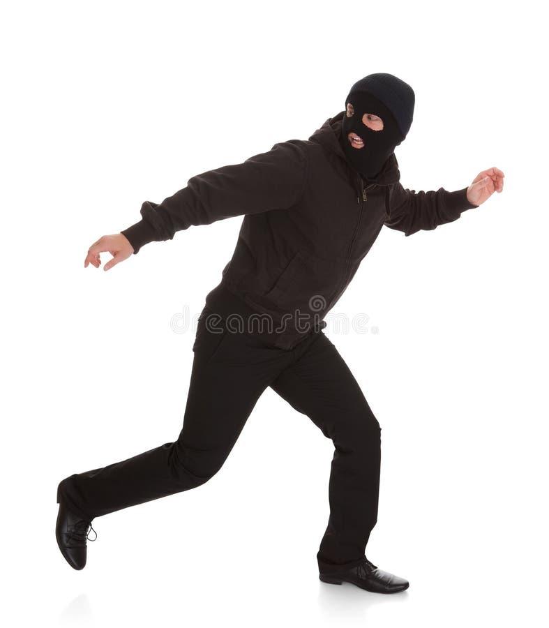 Bandit in black mask running away. Man Wearing Mask Running Over White Background royalty free stock photography