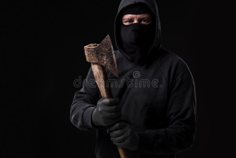 Bandit i svart maskering med handyxan på svart bakgrund fotografering för bildbyråer