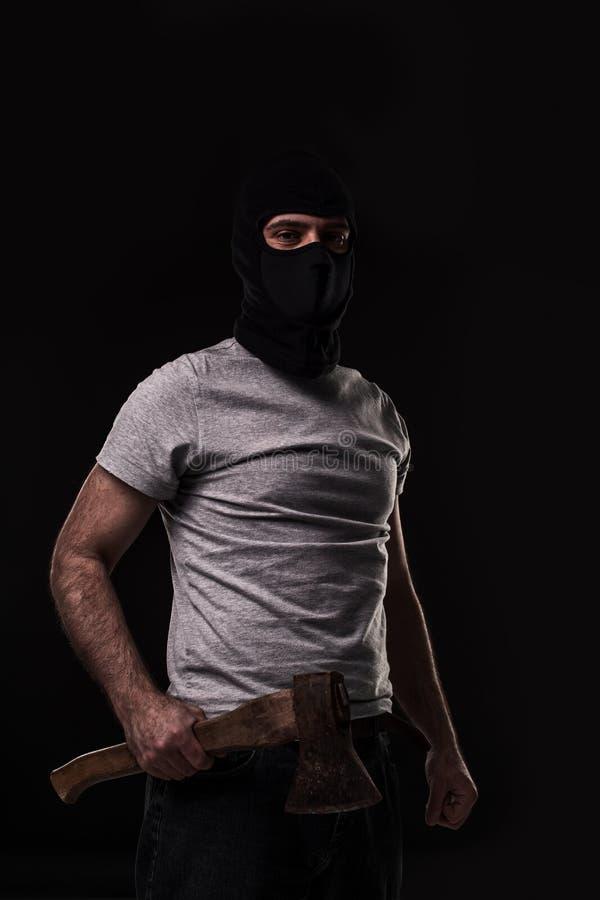 Bandit i svart maskering med handyxan på svart bakgrund royaltyfria bilder