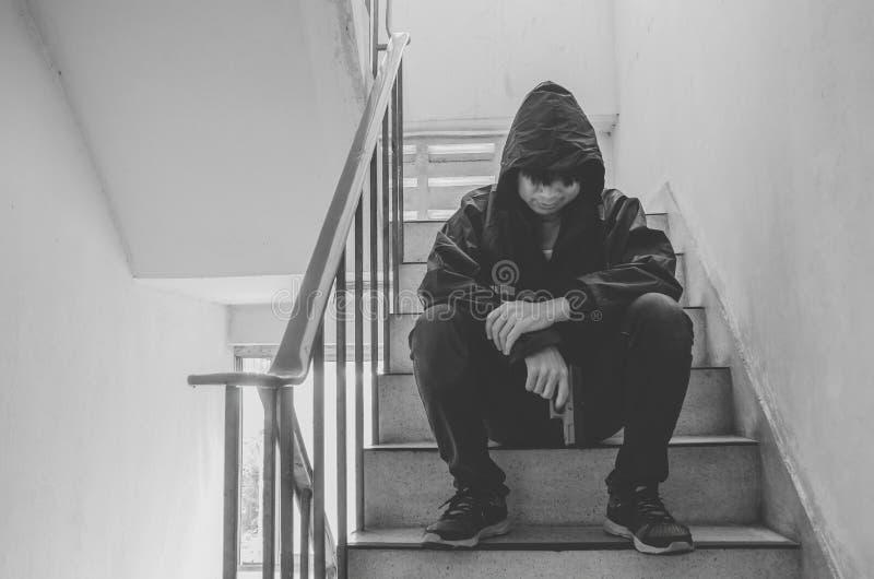 Bandit s'asseyant sur des escaliers, seulement avec ses pensées et ses armes à feu photos stock