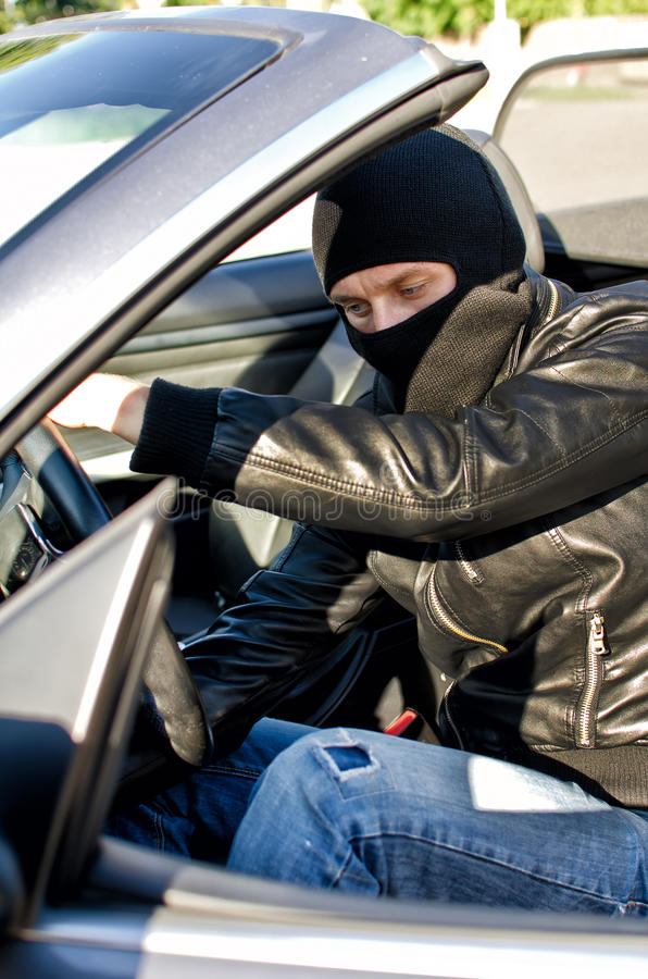 Bandit stealing a car. Bandit in mask stealing a car stock photography
