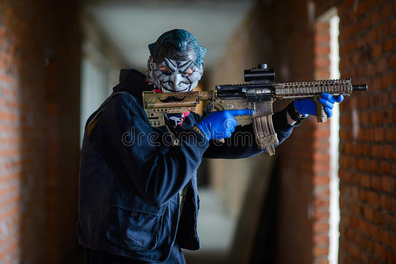 Bandit in terrible mask with gun. Standing in the corridor and looking at camera stock photography