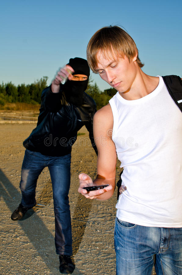 Bandit trying to rob man. Bandit in mask trying to rob young man stock photos
