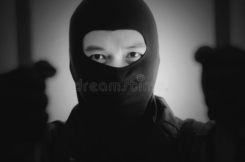 Bandit wearing a mask is agitated prisoner in jail holding bars  on white background. A Bandit wearing a mask is agitated prisoner in jail holding bars  on white royalty free stock photos