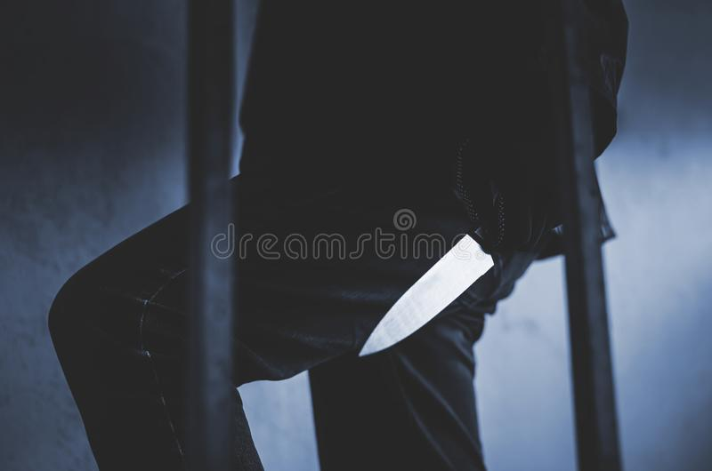 Bandit wearing a mask walking on stairs with a knife for the loot. A Bandit wearing a mask walking on stairs with a knife for the loot royalty free stock photo
