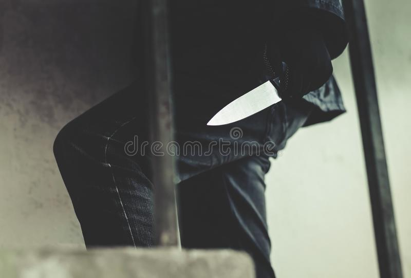 Bandit wearing a mask walking on stairs with a knife for the loot. A Bandit wearing a mask walking on stairs with a knife for the loot stock photography