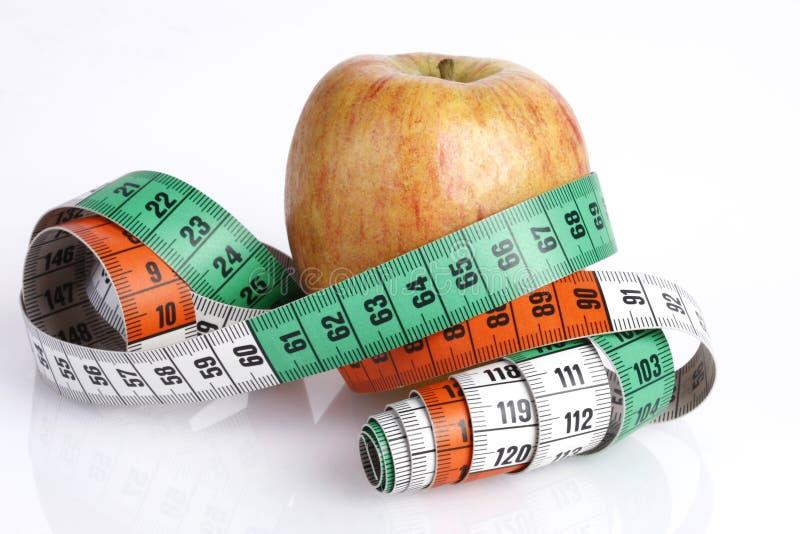 Bandmaß mit Apfel lizenzfreie stockfotos