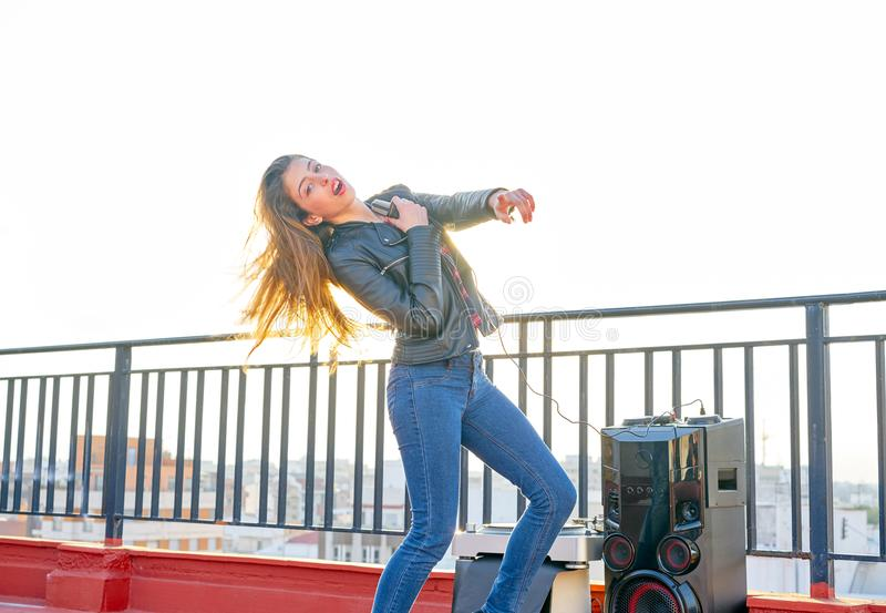 Bandmeisje het zingen karaoke openlucht bij dakterras stock afbeeldingen