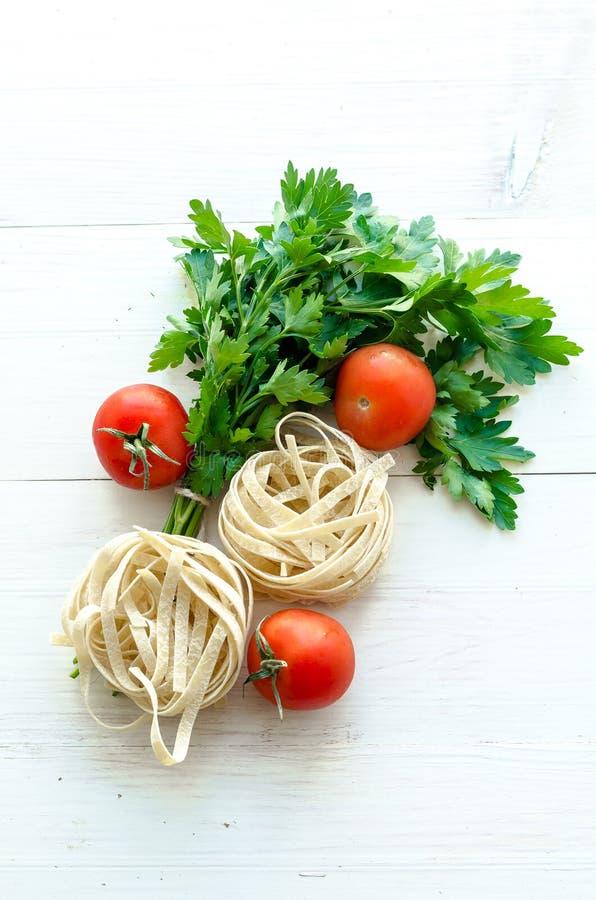 Bandnudeln mit Bestandteilen für das Kochen von Teigwaren Gelockte Petersilie, Knoblauch, Tomaten auf einem Holztisch stockfoto