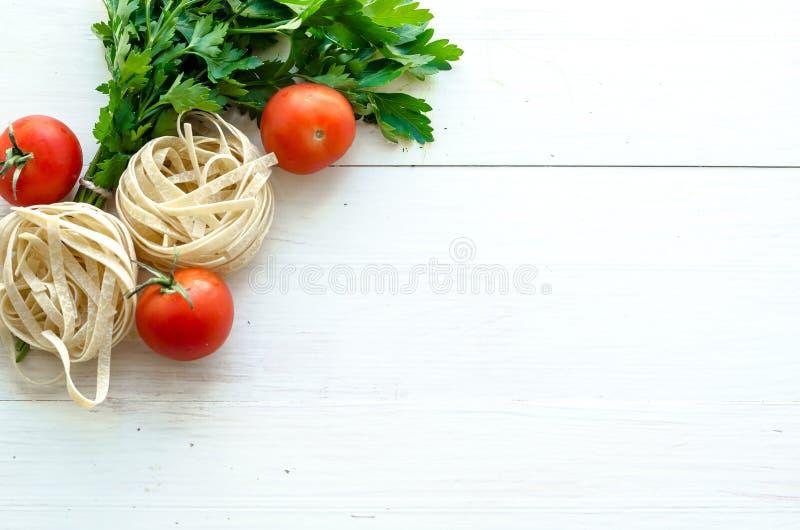 Bandnudeln mit Bestandteilen für das Kochen von Teigwaren Gelockte Petersilie, Knoblauch, Tomaten auf einem Holztisch lizenzfreie stockbilder