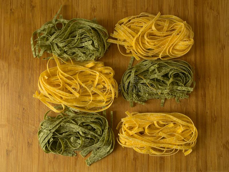 Bandnudeln oder fetuccine gelbe und grüne Teigwaren auf hölzernem t stockbild