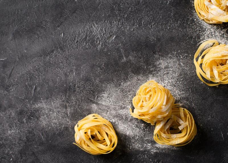 Bandnudelnteigwaren ungekocht, Spaghettihintergrund machend stockfoto