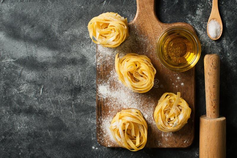 Bandnudelnteigwaren ungekocht, Spaghettihintergrund machend, schwarze Beschaffenheit stockfotografie