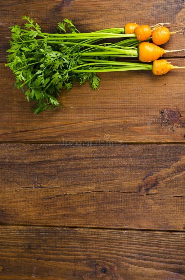 Bando de cenouras pequenas e redondas (Cenouras Heirloom Parisienses) sobre fundo de madeira fotografia de stock