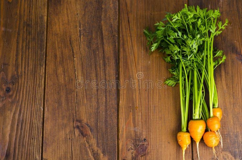 Bando de cenouras pequenas e redondas (Cenouras Heirloom Parisienses) sobre fundo de madeira foto de stock