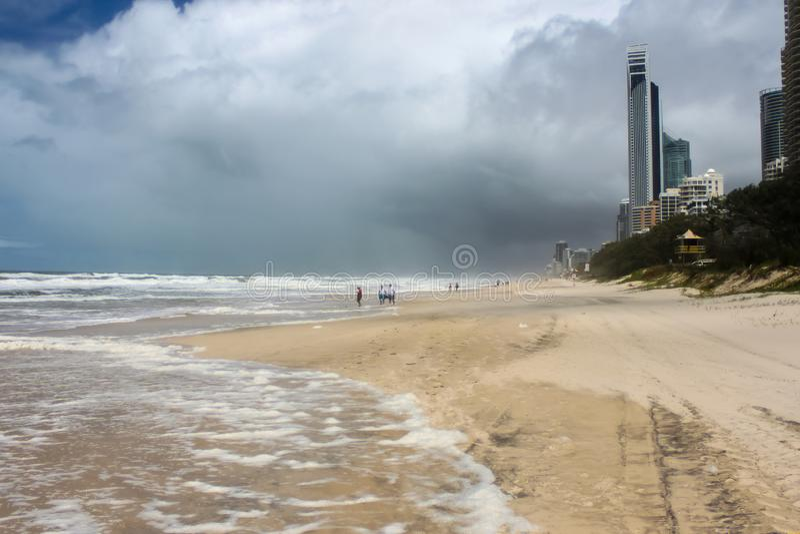 Bandsporen en niet identificeerbare toeristen die op strand uit in branding op stormachtige dag met donkere wolken in Gold Coast  stock foto's