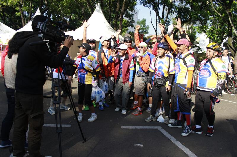 Bandung-Indonesia;  The cameraman is recording video and interviewing the winner of a bicycle sport. stock photos