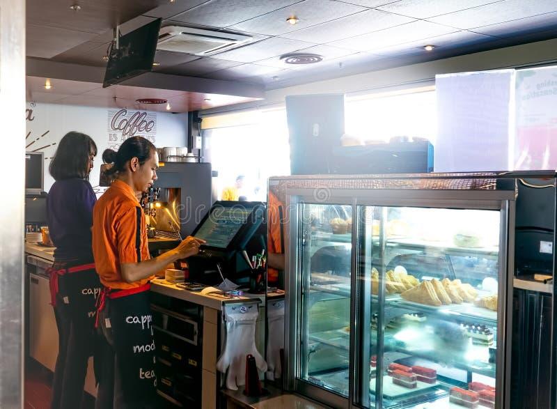 Bandung 1 Juli 2019: Barista och kassörska Preparing Customer Order i kaffehus eller att shoppa med kylskärm royaltyfri fotografi